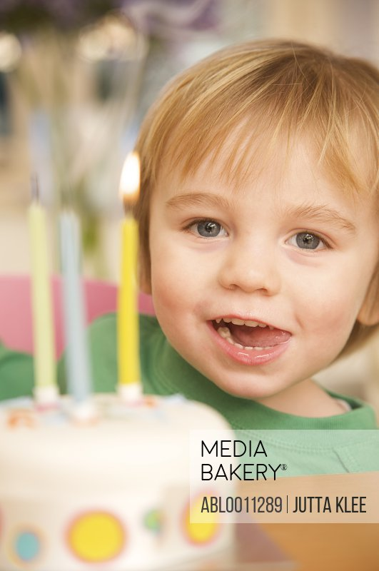 Toddler and birthday cake with three candles