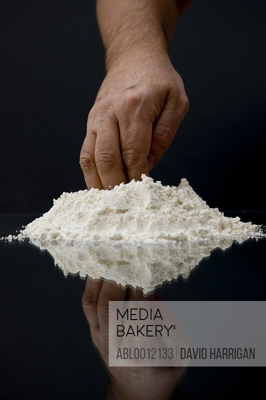 Close up of a man hand with fingers in a heap of flour