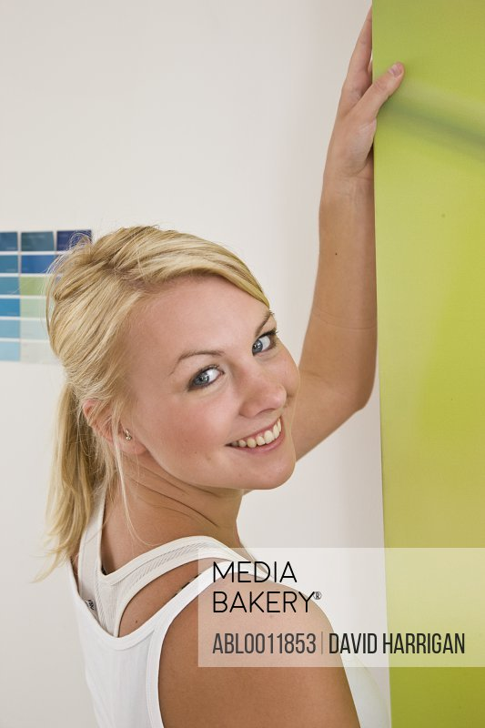 Close up of a smiling woman holding and hanging a canvas on a wall