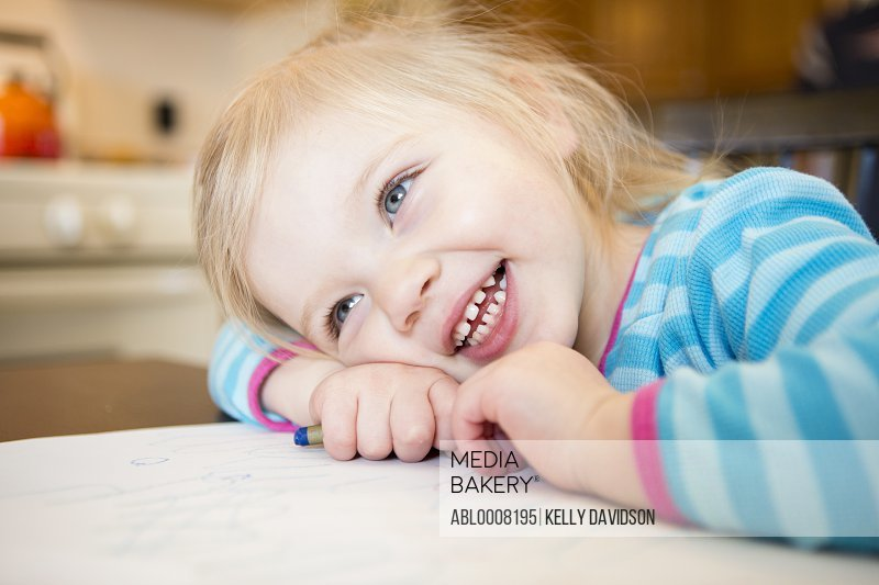 Smiling Girl Resting Head on Table