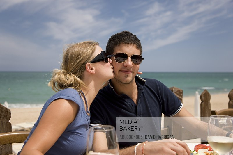Young couple having lunch al fresco by the sea - woman kissing man on the cheek