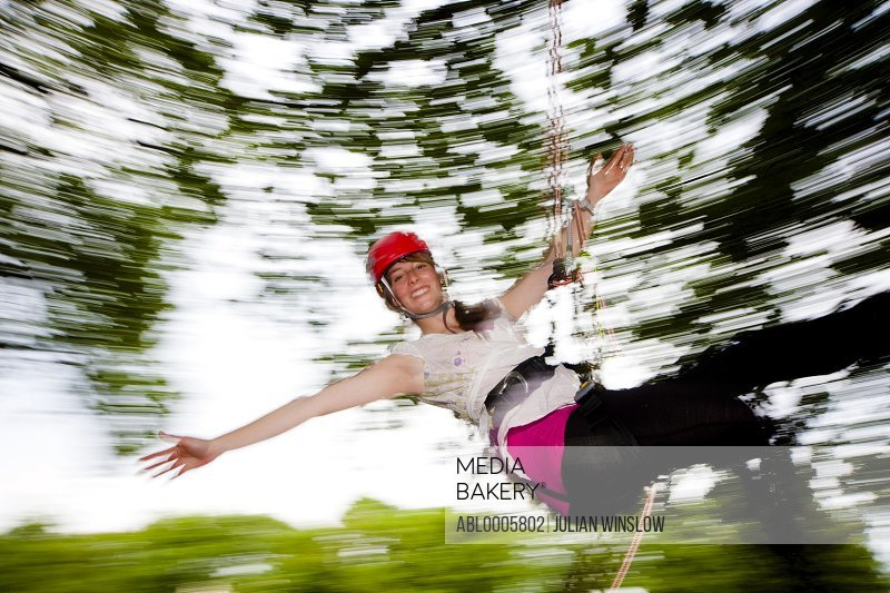 Woman dangling from a rope suspended mid air - blurred motion