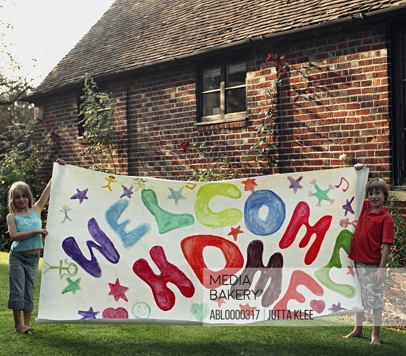 Portrait of two young children holding colorful welcome home sign