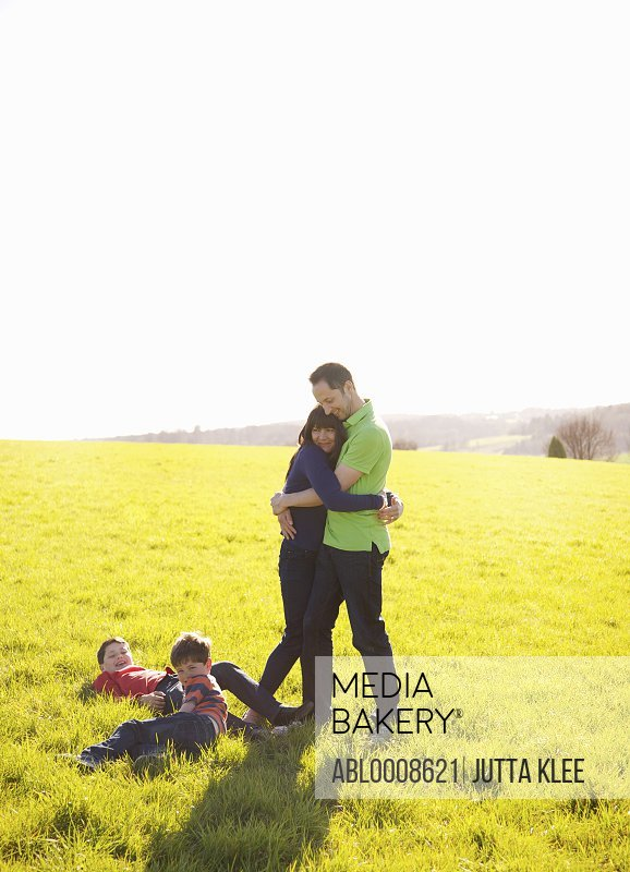 Couple Hugging on Field and Children Lying on Grass