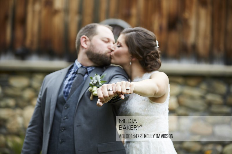 Bride and Groom Kissing and Showing their Wedding Rings