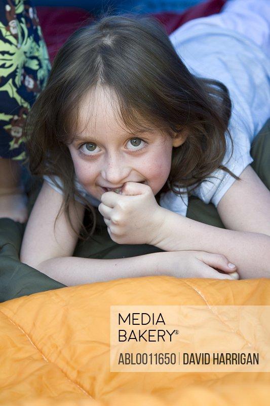 Young girl lying inside tent