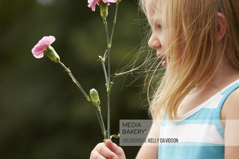 Profile of Young Girl Holding Pink Carnations