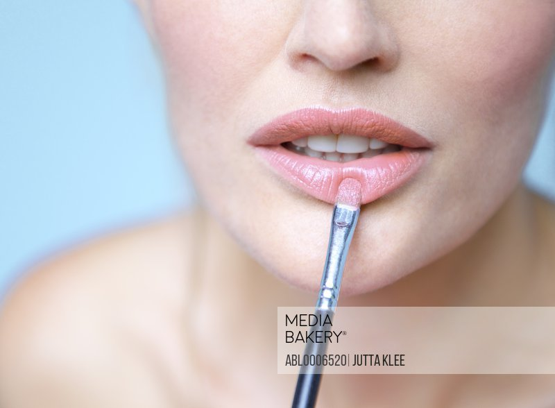 Woman Applying Lipstick with Makeup Brush - Close-up view