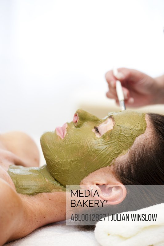 Beautician hand applying green facial mask on woman face