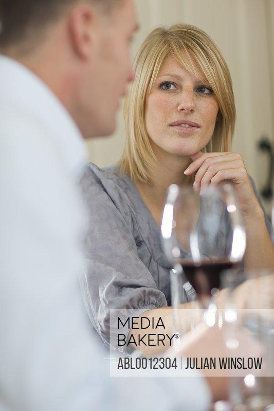 Woman sitting at a dining table looking at man