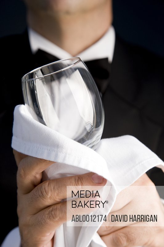 Close up of a waiter polishing a wine glass with a white napkin