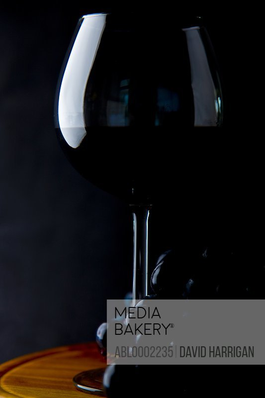 Glass of Red Wine and Black Wine Grapes
