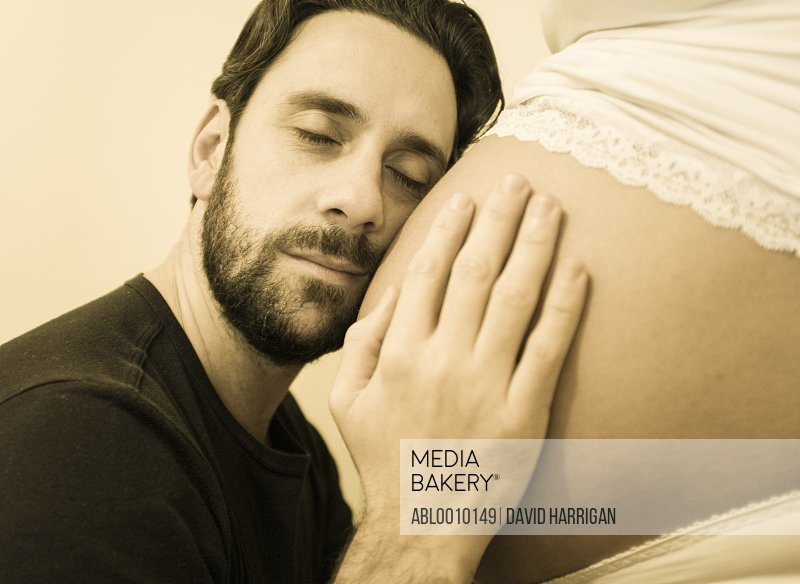 Man Resting Face on Pregnant Woman Belly