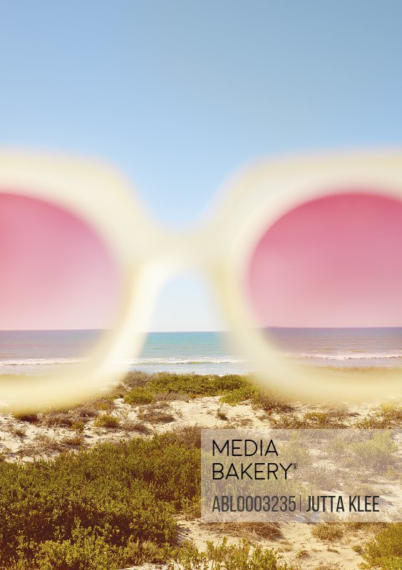 Cropped View of Rose-Coloured Sunglasses with Beach in the background