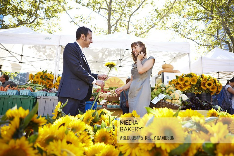 Man Giving Flower to Woman at Farmers Market