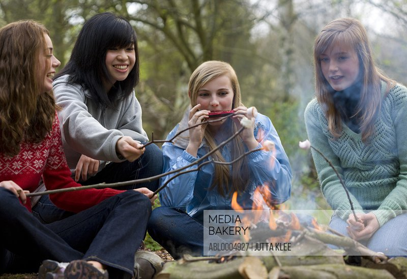 Teenage girls roasting marshmallow over campfire one is playing the harmonica