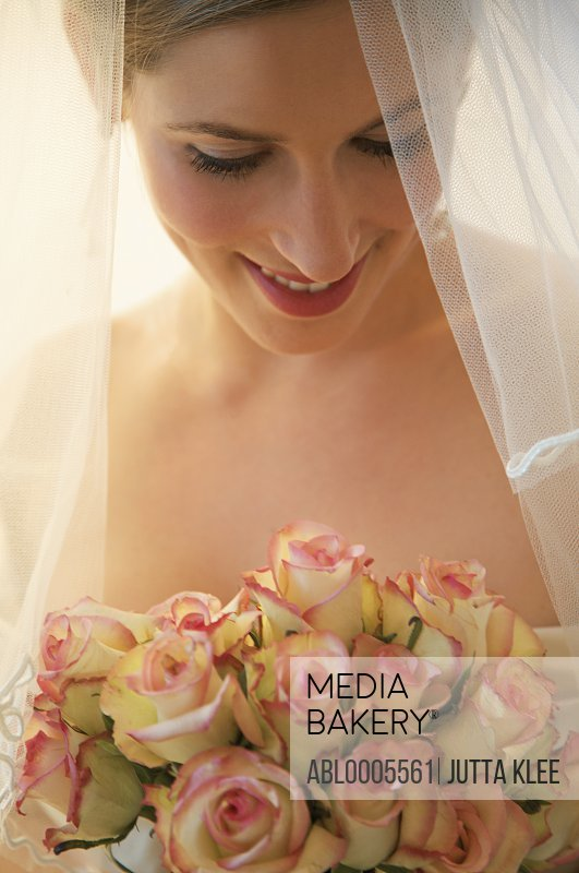 Blushing bride wearing a veil and holding a bouquet of roses