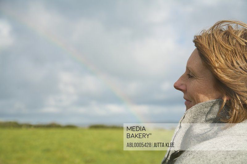Close up of a woman standing in a field looking at the rainbow
