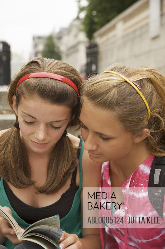 Two teenaged girls inspecting a city map