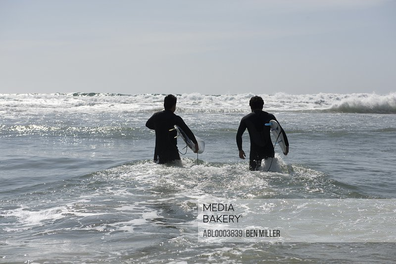 Back view of Two Male Surfers Walking into the Sea