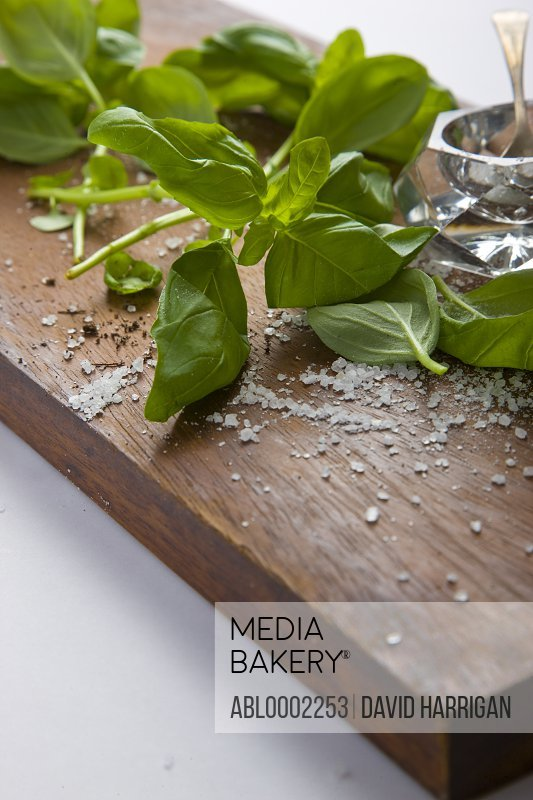 Basil Leaves and Rock Salt on Wooden Cutting Board