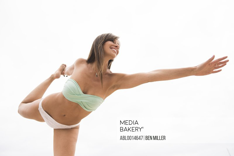 Woman on Beach with Arms Raised Standing on one leg