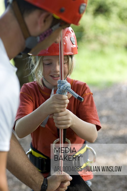 Young girl holding onto climbing rope with man helping her