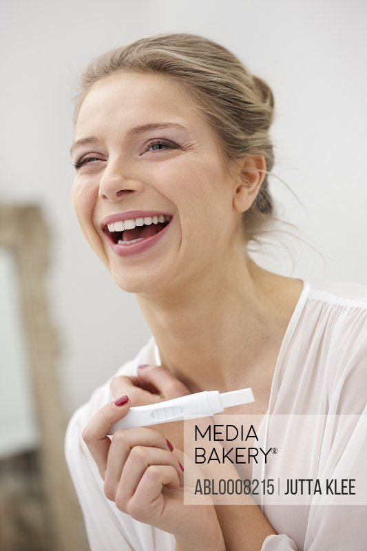 Smiling Woman Holding Pregnancy Test