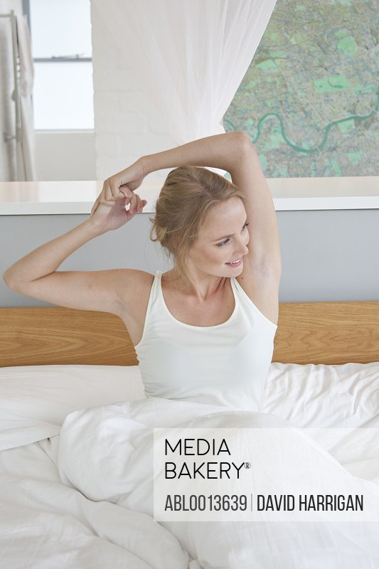 Woman Sitting in Bed Stretching her Arms