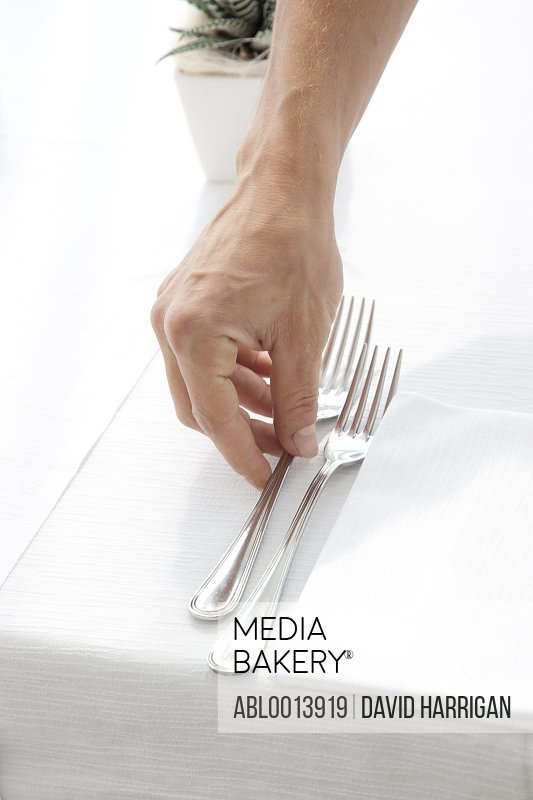 Close up of Waiter's Hand Arranging Cutlery on Restaurant Table