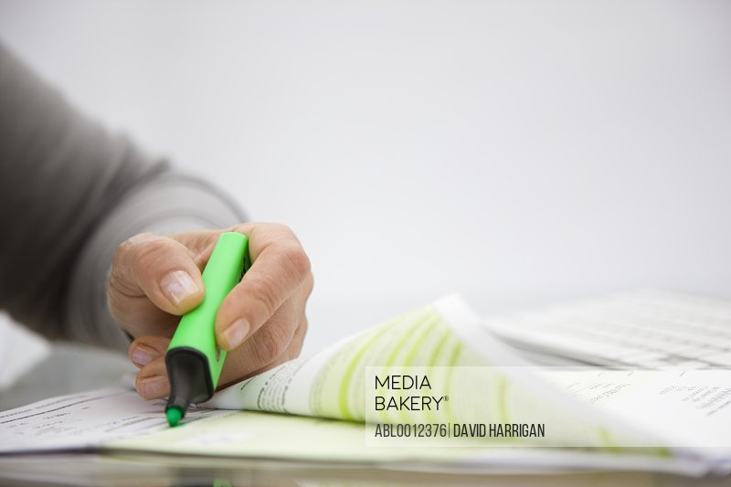 Close up of a woman hand holding a green highlighter over a paper document