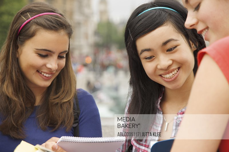 Three smiling teenaged girls reading, writing and holding note pads