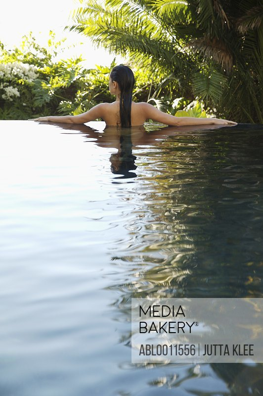 Back of young woman standing in an exotic swimming pool with arms stretched