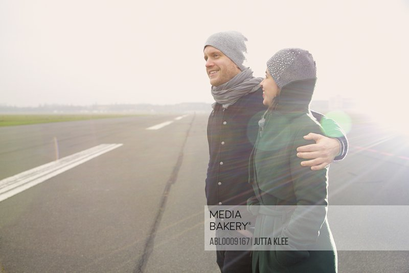 Smiling Couple Standing on Airport Runway