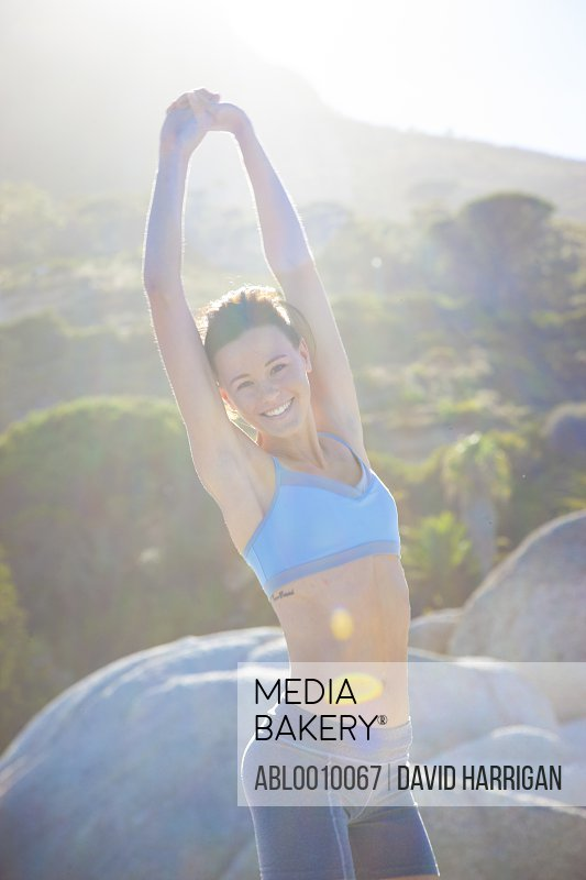 Woman Stretching Arms Outdoors Smiling