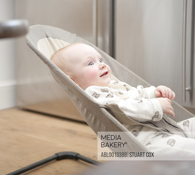 Smiling Baby Lying on Rocking Chair