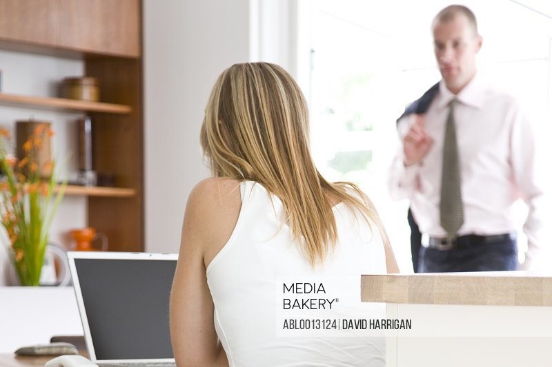 Back View of Woman Using Laptop with Businessman in Background