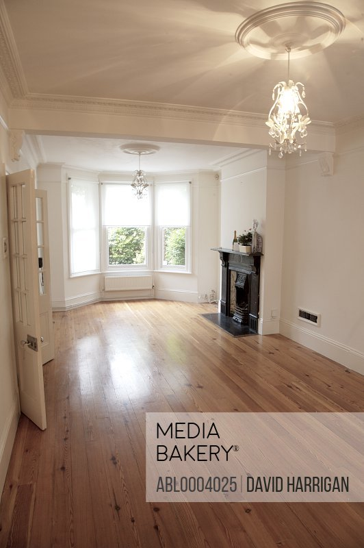 Empty room with fireplace and bay window