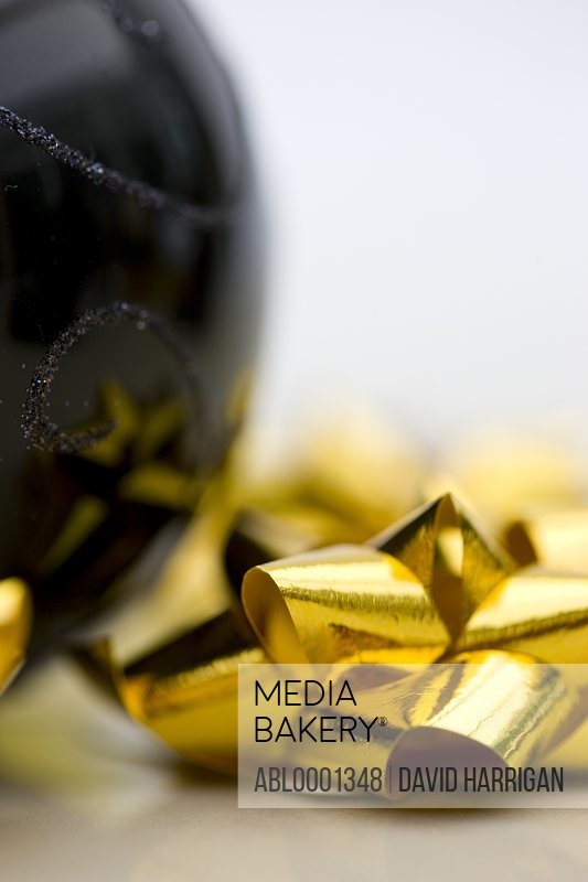 Close up of a black Christmas bauble and gold bow