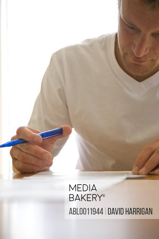 Close up of a man signing documents