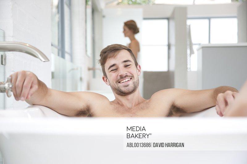 Smiling Man in Bathtub, Woman in Background