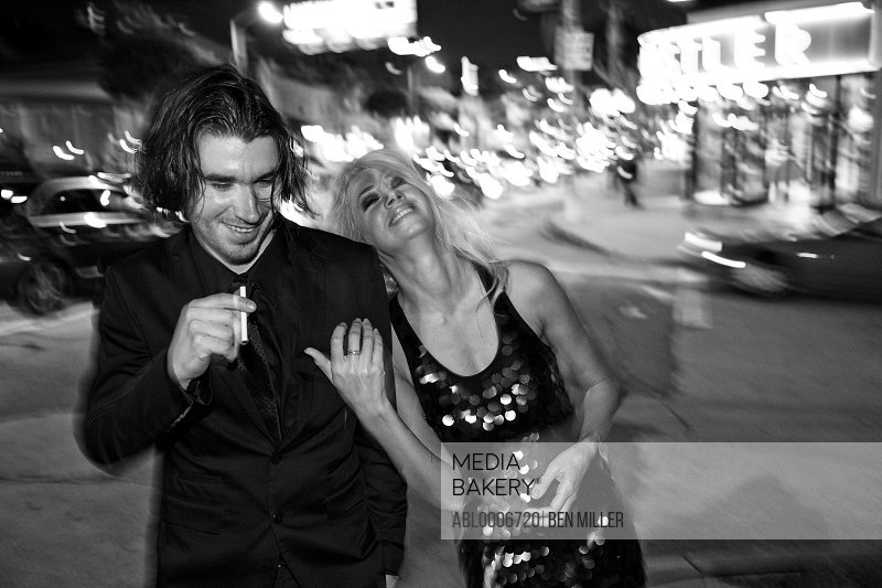 Laughing Couple Walking on City Street at Night