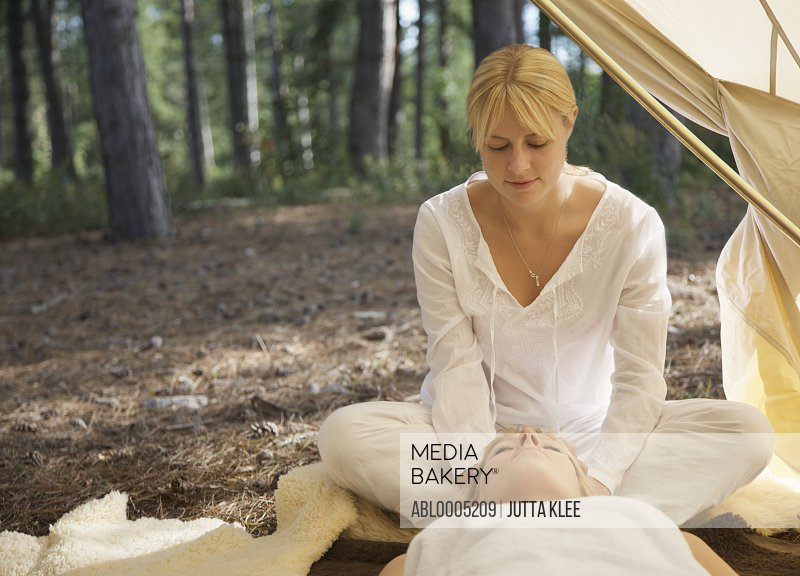 Massage therapist sitting behind a woman massaging her scalp under a tent in a forest
