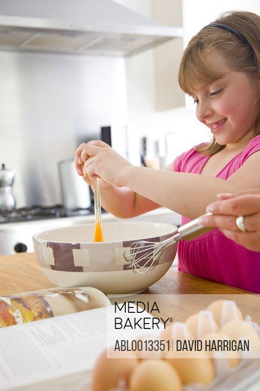 Girl Breaking an Egg into a Bowl
