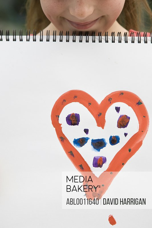 Young girl holding art book with heart on