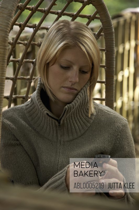 Young woman sitting on a hanging rattan chair using cell phone