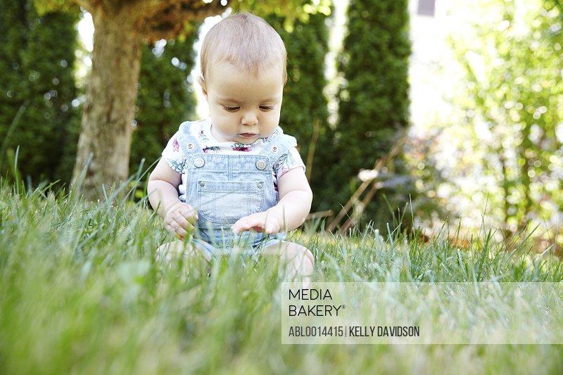 Baby Girl Sitting on Grass in Garden