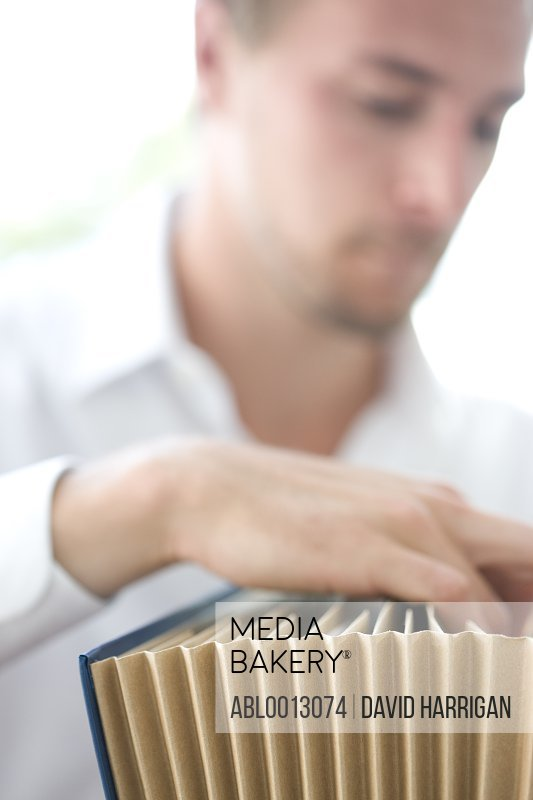 Close up of Businessman Flicking through File Folder