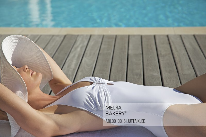 Woman in white hat and swimsuit lying by edge of swimming pool