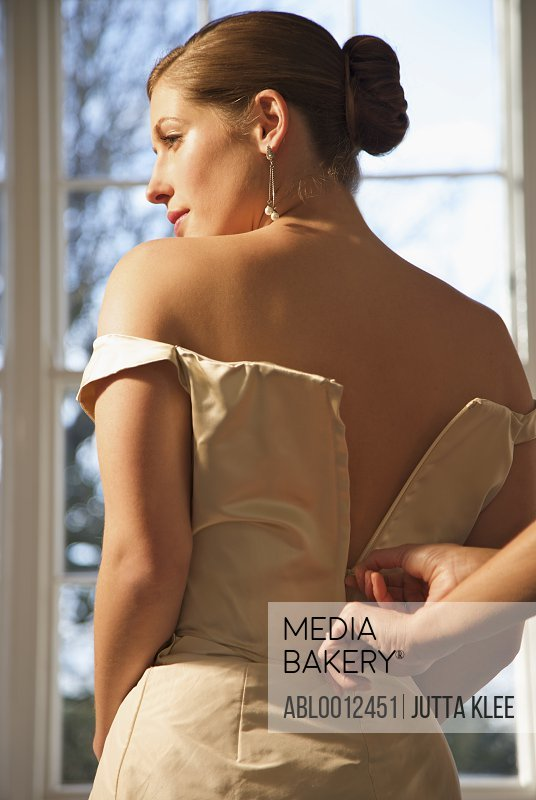 Woman hands unzipping the back of a bride wedding gown